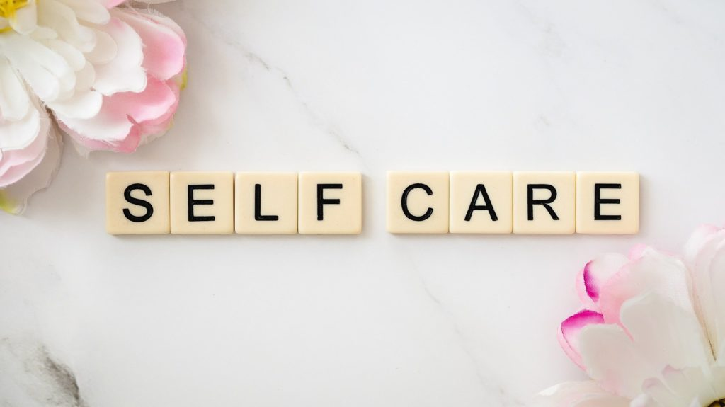 Self Care image spelled out in tiles with flowers